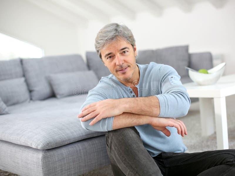 成熟人坐地板放松 免版税图库摄影