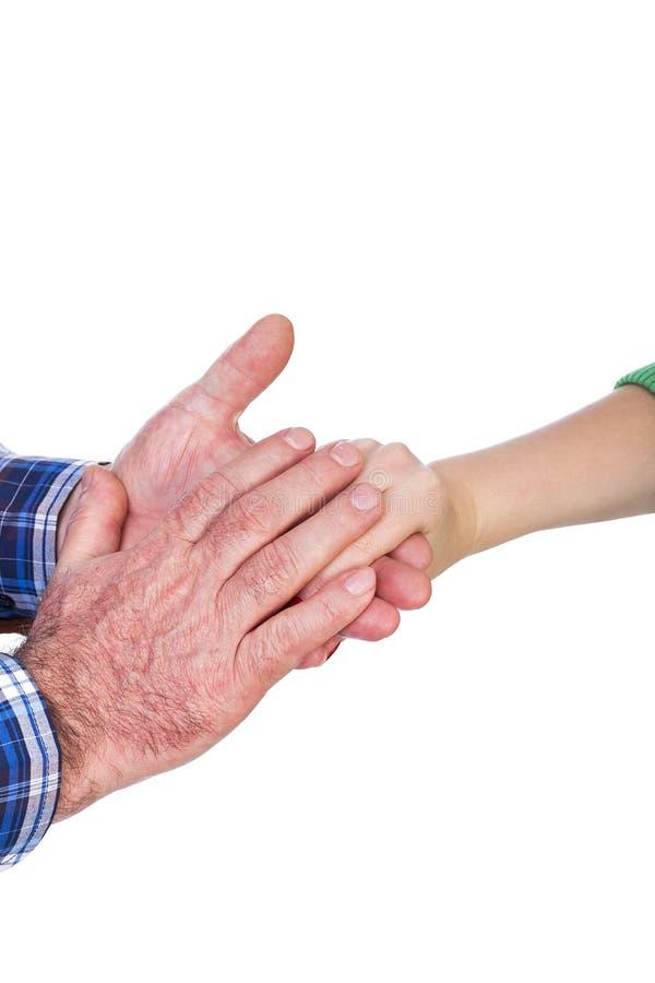 成熟人特写镜头递握他的女儿手,浓缩的关心 免版税库存图片