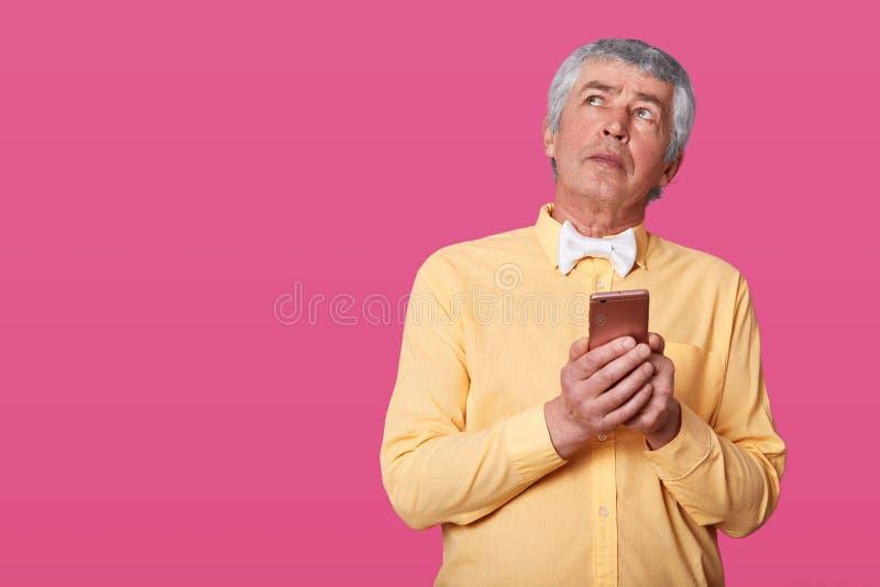 成熟人画象安排皱痕和灰色头发穿戴在黄色衬衣和白色蝶形领结,在手上拿着智能手机,神色 免版税库存图片