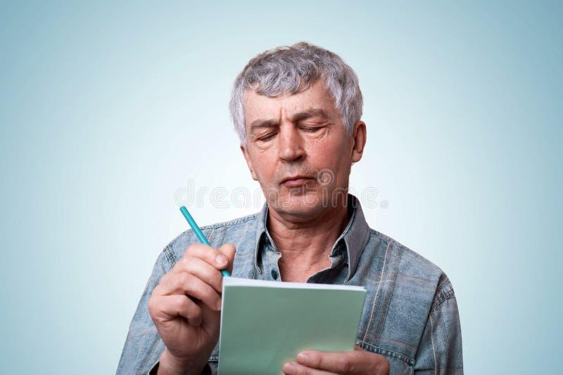 成熟人画象有灰色拿着笔记本和笔在他的手上的头发佩带的斜纹布时髦的衬衣的做有有些的笔记 库存图片