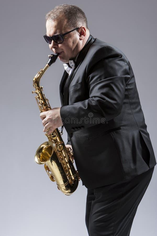 成熟传神白种人萨克斯管音乐家画象  库存图片