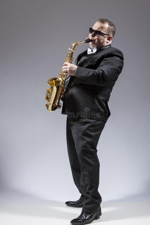 成熟传神白种人萨克管演奏员全长画象  库存照片