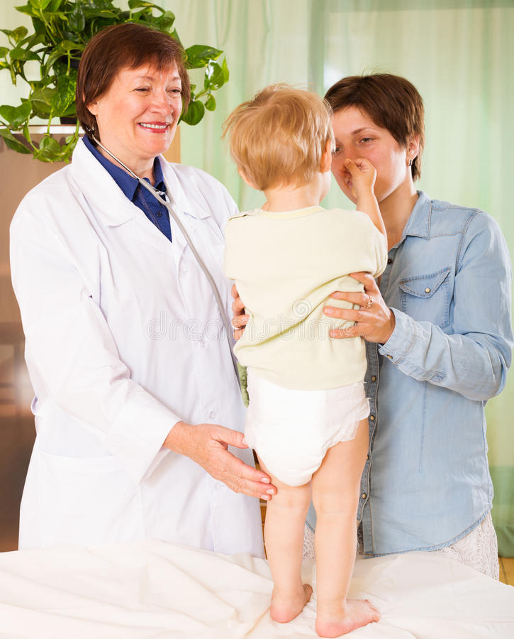 成熟儿科医生医生审查的小孩 库存图片