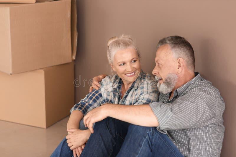 成熟加上移动的箱子坐地板在新的家 图库摄影