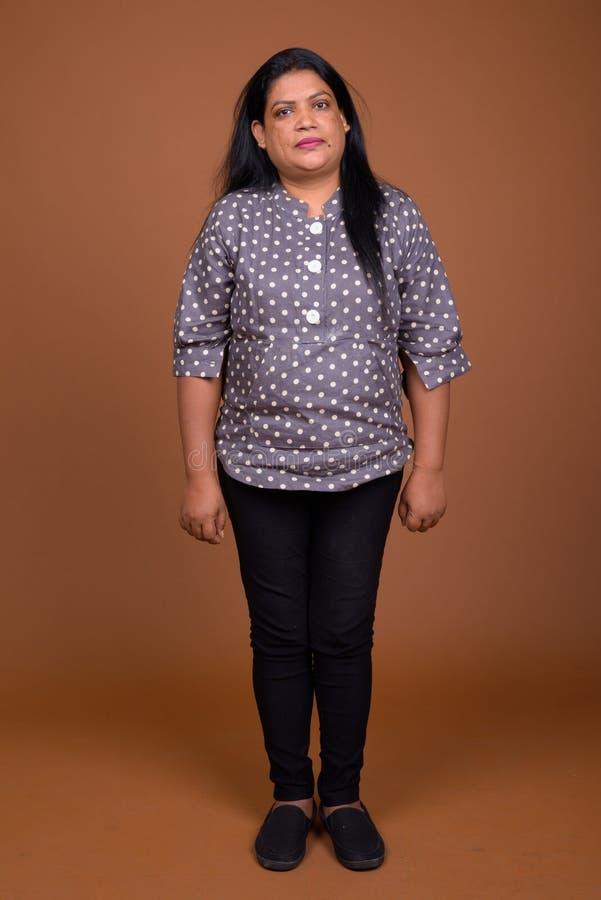成熟印地安妇女画象反对棕色背景的 免版税库存照片