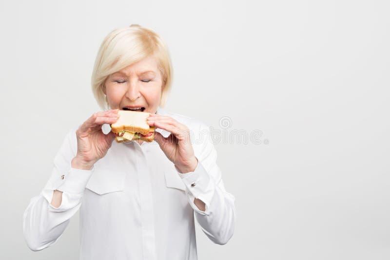 成熟和满意的妇女吃着她的自创三明治高兴地 她准备有这顿膳食第一叮咬  库存图片