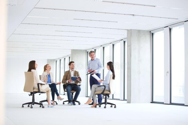 成熟商人谈论与椅子的同事在空的办公室 免版税库存照片