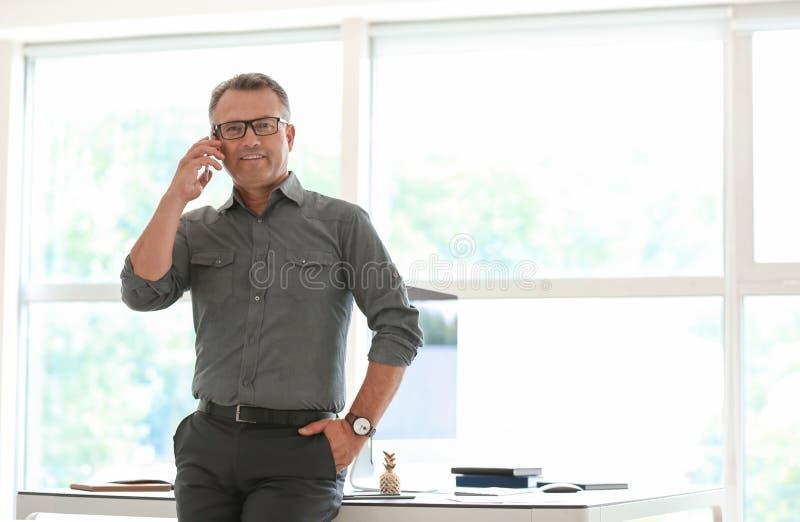 成熟商人谈话由手机在办公室 免版税库存图片