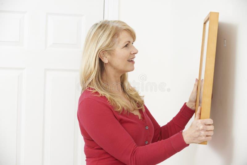 成熟在墙壁上的妇女垂悬的图片 库存照片