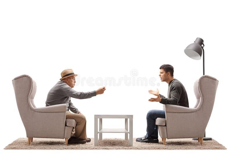 成熟在扶手椅子争论安装的人和一个年轻人 免版税库存图片