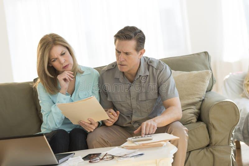 成熟在沙发的夫妇计算的家财务 库存图片