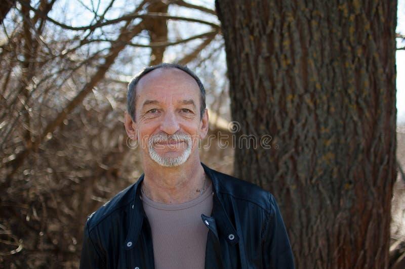 成熟在站立户外在树附近的黑暗的皮夹克的老人和胡子男性画象有灰色头发的  库存照片
