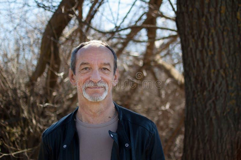 成熟在站立户外在树附近的黑暗的皮夹克的老人和胡子男性画象有灰色头发的  库存图片