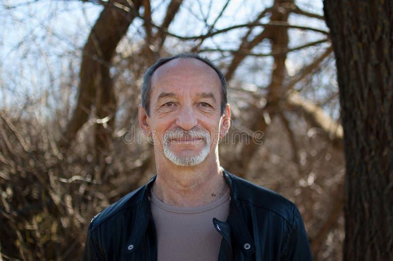 成熟在黑暗的皮夹克身分的老人和胡子户外画象有灰色头发的在蓝色的树附近 库存图片