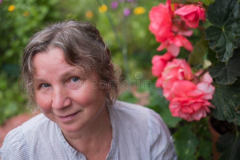 成熟坐在她的庭院里的白种人妇女在花附近 库存图片