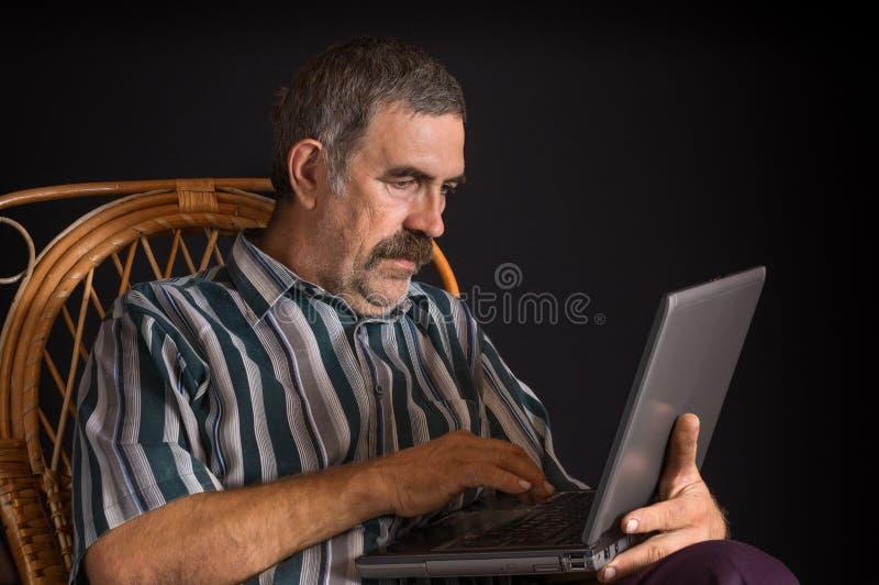 成熟坐在藤椅和键入在膝上型计算机个人计算机的乌克兰农民 免版税库存照片