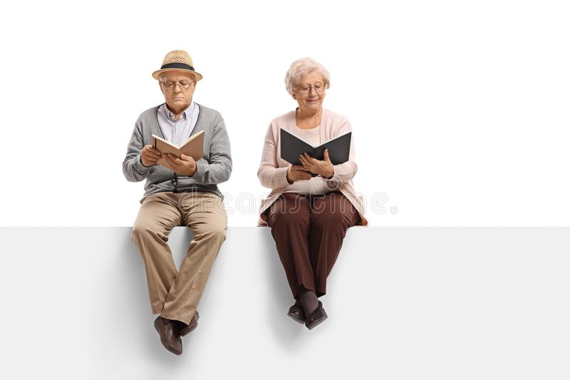 成熟坐盘区和读b的男人和一名年长妇女 免版税图库摄影