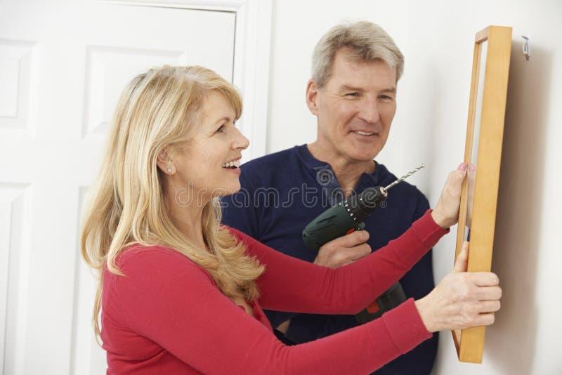 成熟垂悬画框的夫妇钻墙壁 免版税库存照片