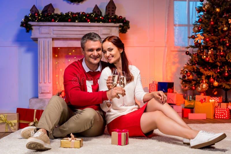 成熟夫妇使叮当响的香槟玻璃 免版税图库摄影