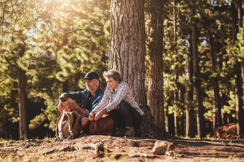 成熟夫妇在与背包和指南针的一棵树下 库存图片