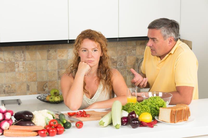 成熟夫妇在厨房里 免版税图库摄影