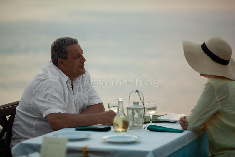 成熟夫妇的浪漫晚上在沿海岸区餐馆 库存照片