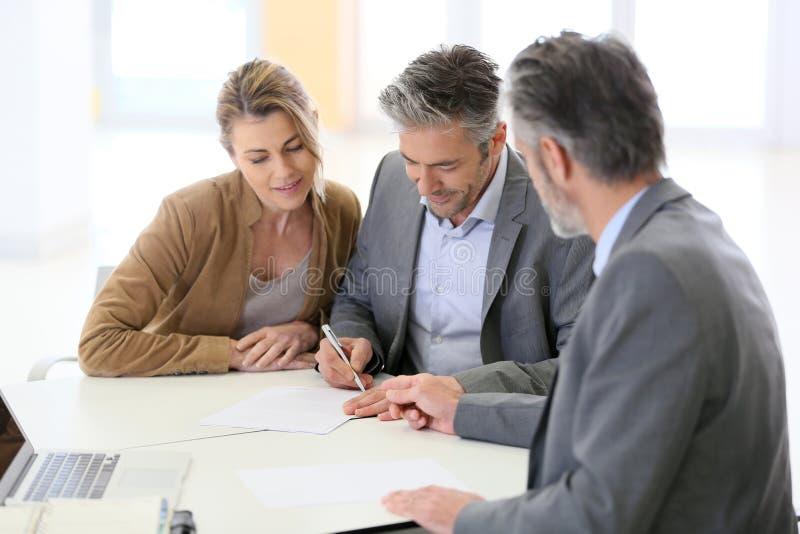成熟夫妇签署的合同 库存图片