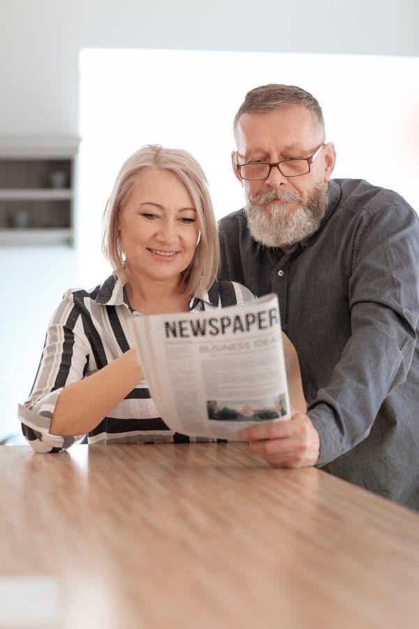 成熟夫妇读书报纸在家 免版税库存图片