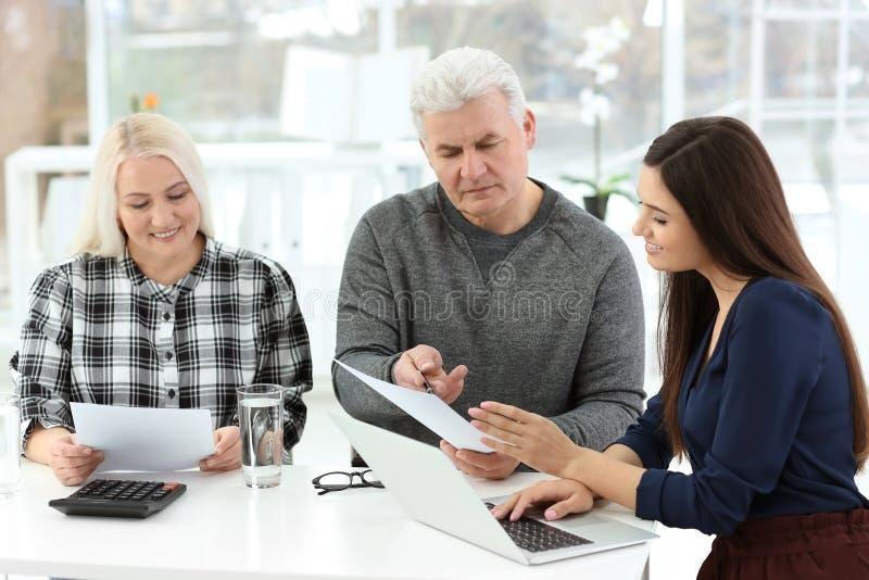 成熟夫妇谈论退休金与顾问在办公室 库存照片