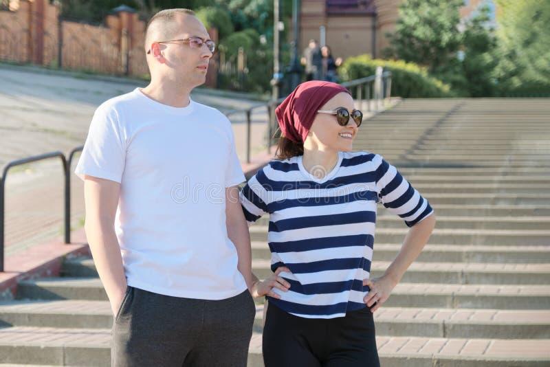 成熟夫妇谈话在台阶、微笑的愉快的男人和妇女附近 图库摄影