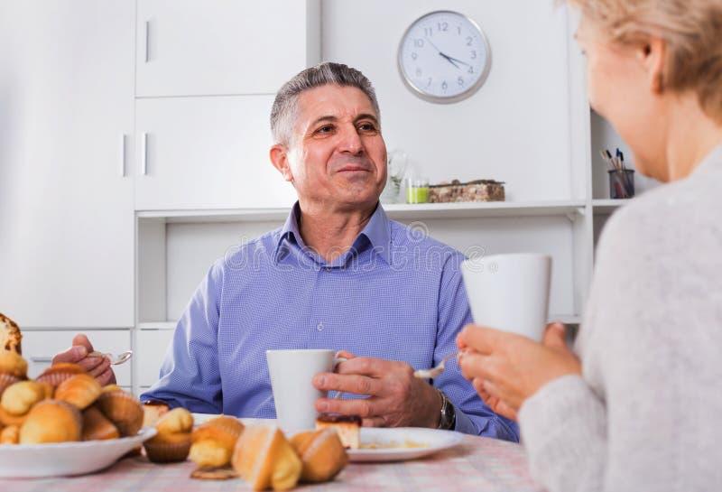 成熟夫妇食用一顿下午快餐用新松饼和cak 免版税库存图片