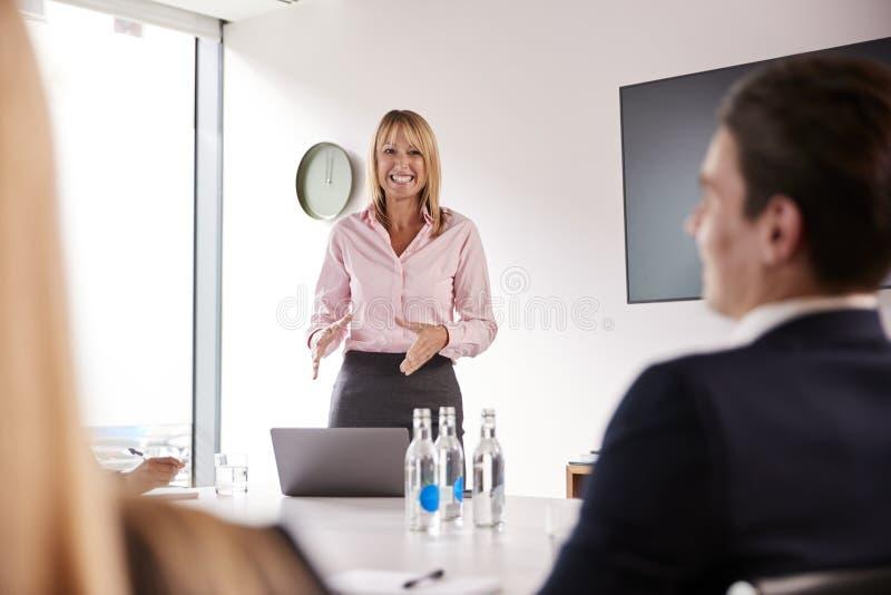 成熟女实业家对小组聚会演讲在表附近毕业生补充评估天 免版税库存照片