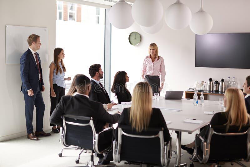 成熟女实业家对小组聚会演讲在表附近毕业生补充评估天 免版税库存图片