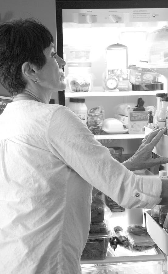 成熟女性看在冰箱 免版税图库摄影