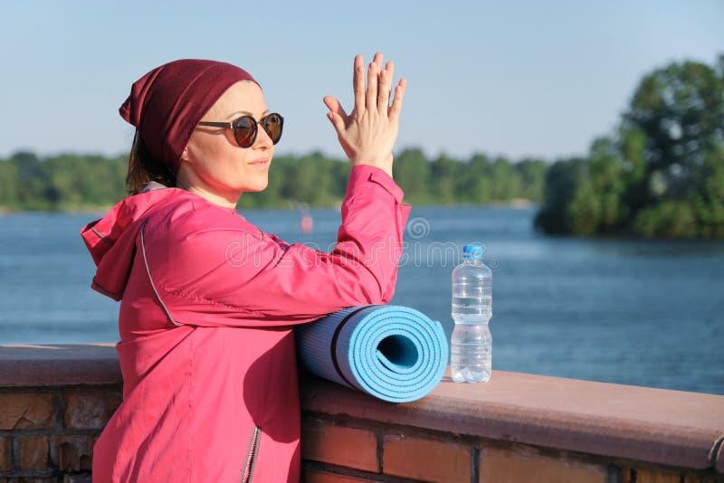成熟妇女、室外画象运动服的年龄女性有瑜伽席子的和瓶健康生活方式水 库存照片