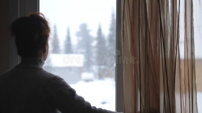 成熟妇女剪影年迈的观看的在多雪的山的窗口里 免版税库存图片