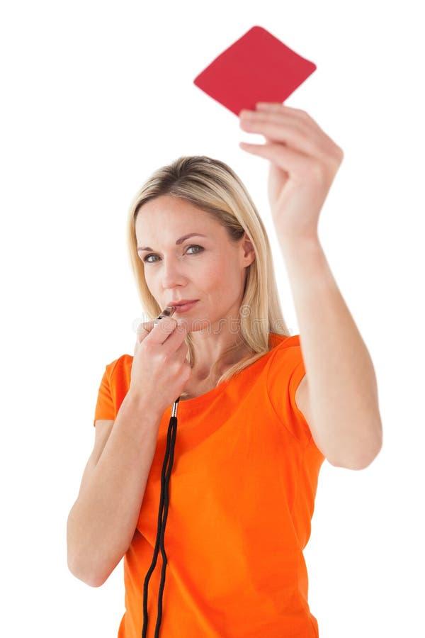 成熟妇女吹的口哨和拿着红牌 库存图片