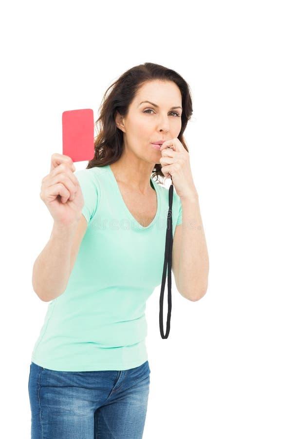 成熟妇女吹的口哨和拿着红牌 免版税库存图片