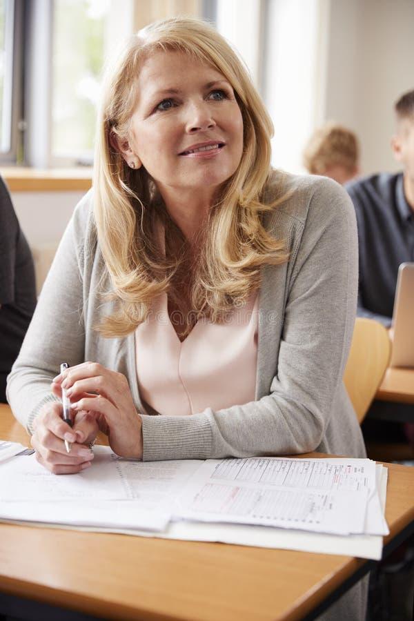 成熟妇女在上成人教育类的学院 免版税图库摄影