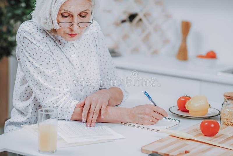 成熟妇女在家创造食物食谱 免版税库存图片