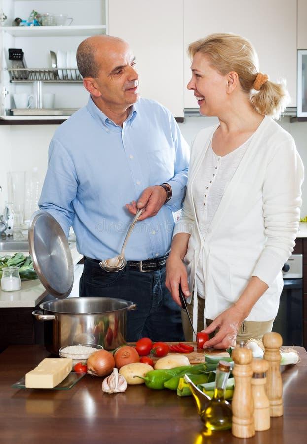 成熟妇女微笑和与爱的前辈的厨师菜 免版税库存照片