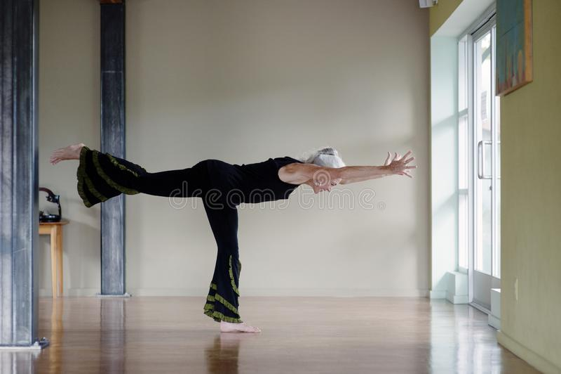 成熟妇女战士III瑜伽姿势 免版税库存图片