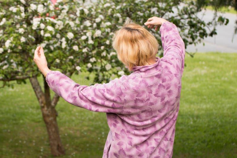 成熟妇女拥抱果树 免版税库存照片