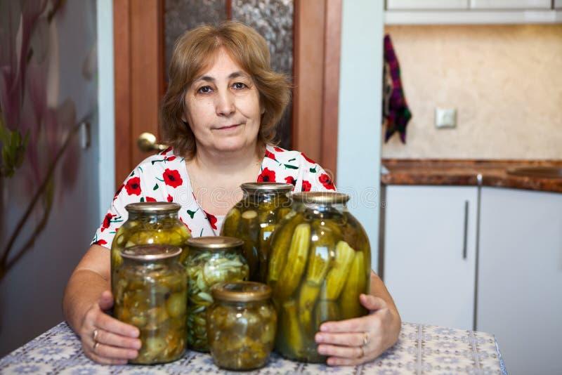 成熟妇女拥抱玻璃瓶子用用卤汁泡的黄瓜,当坐在自己的国内厨房里时 免版税图库摄影