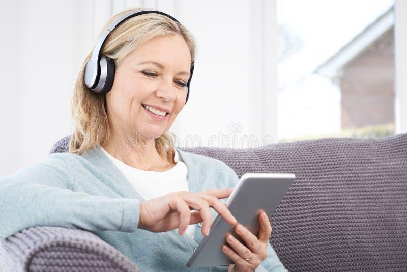 成熟妇女放出从数字式片剂的音乐到无线Headp 免版税库存照片