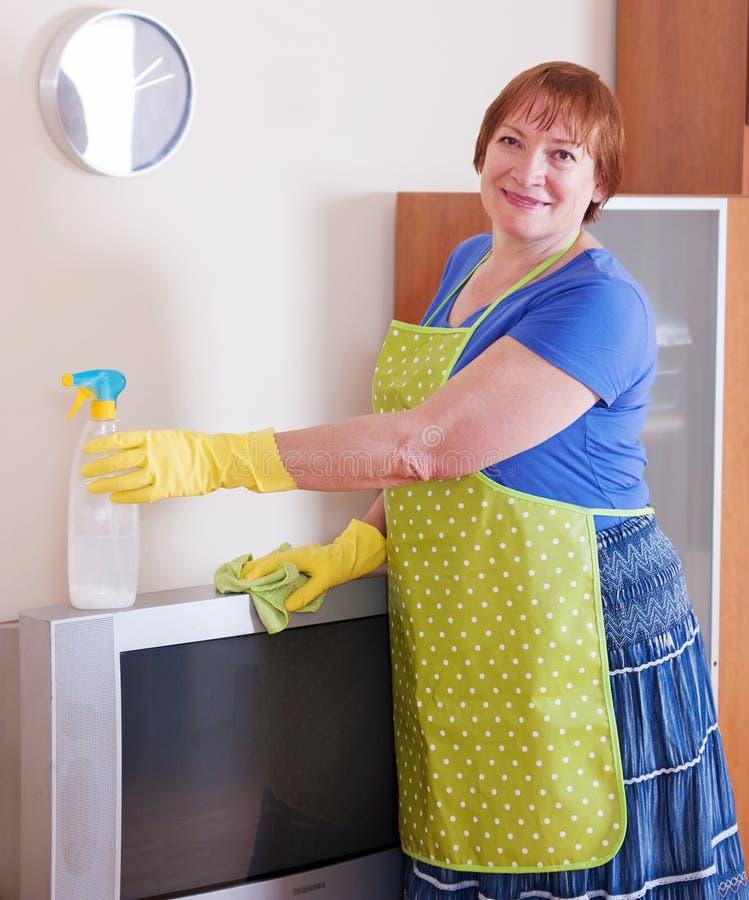 成熟妇女清洗房子 免版税图库摄影