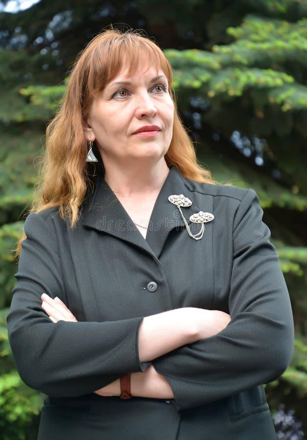 成熟妇女的画象一件黑夹克的用横渡的手 库存照片
