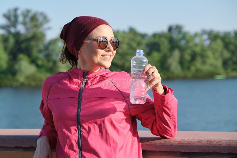 成熟妇女,年龄女性的室外画象健康生活方式运动服的有瑜伽席子的,从瓶的饮用水 免版税库存照片