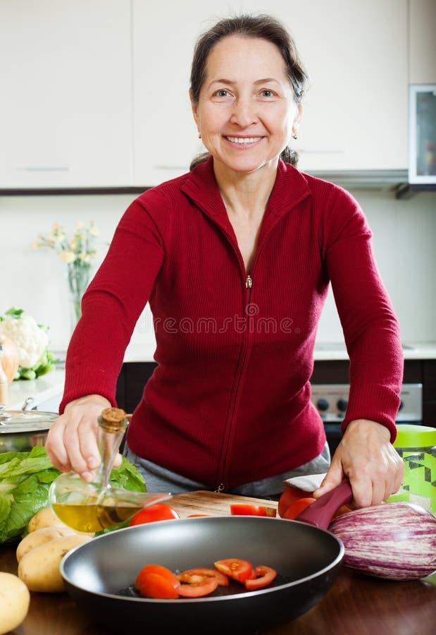 成熟对煎锅的妇女倾吐的油 免版税库存图片