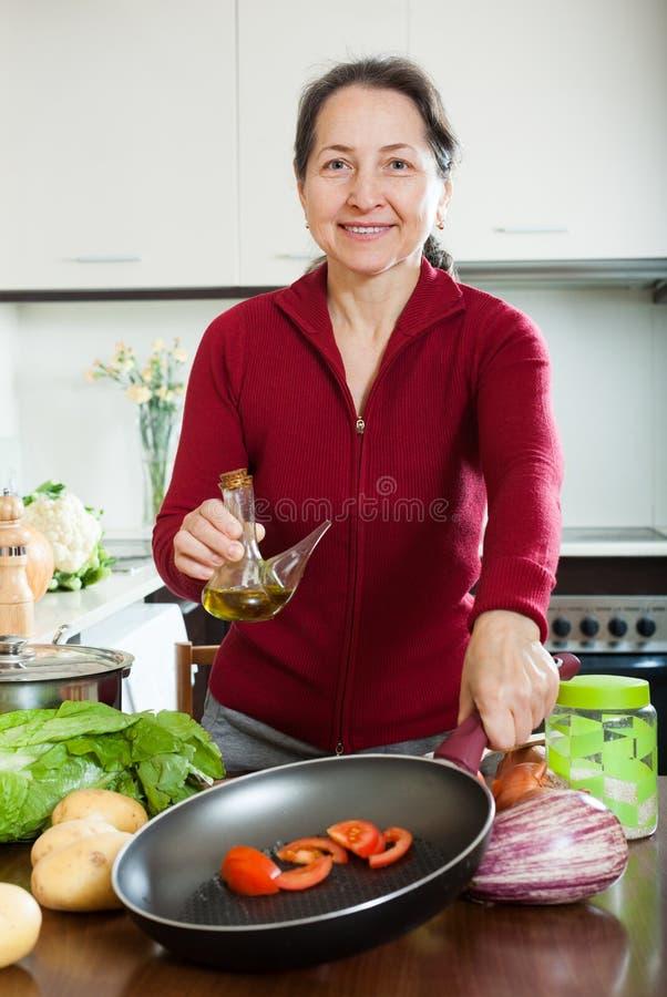 成熟对煎锅的妇女倾吐的油 图库摄影